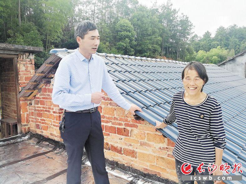 喻伟江(左)来到深度贫困户周冬泉的家,爬上楼顶检查新铺的瓦片是否漏水。  长沙晚报全媒体记者 张禹 摄