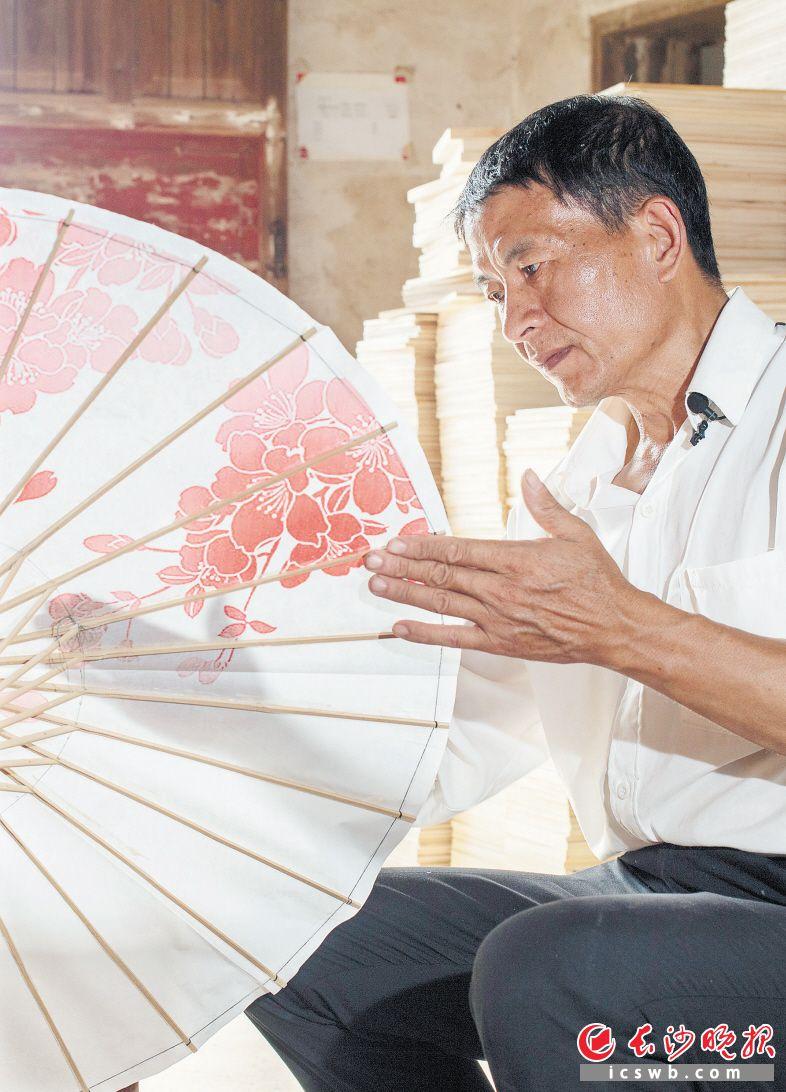 15岁开始学习制作油纸伞的李忠国,通过技术改良,将传统加工的72道工序简化为14道。均为长沙晚报全媒体记者 罗杰科 摄